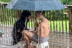 Siblings Share Umbrella in the Rain