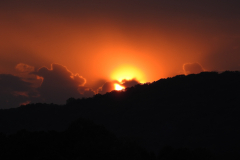 Fiery Sun Sets behind Mountains